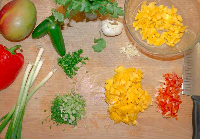 ingrediants for mango salsa being chopped on cutting board