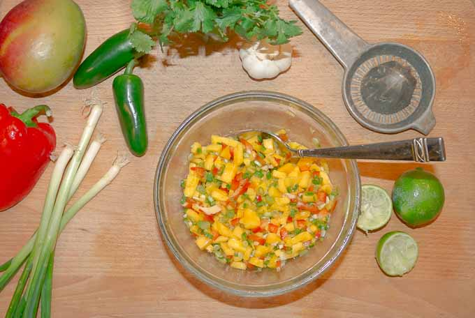 mango salsa in mixing bowl on wood cutting board