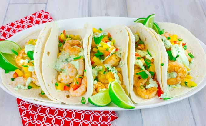 5 Spicy Shrimp Tacos with Mango Salsa on white oval platter