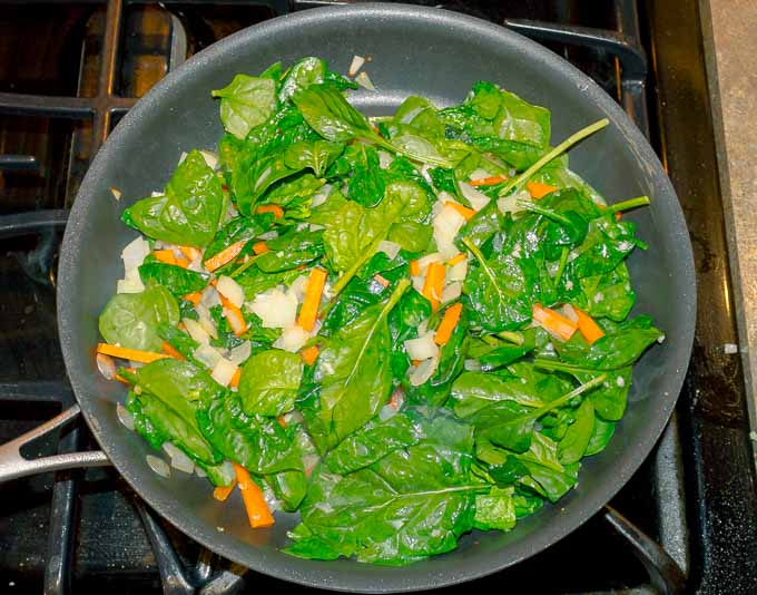 spinich, carrot, and onion being sauteed in skillet