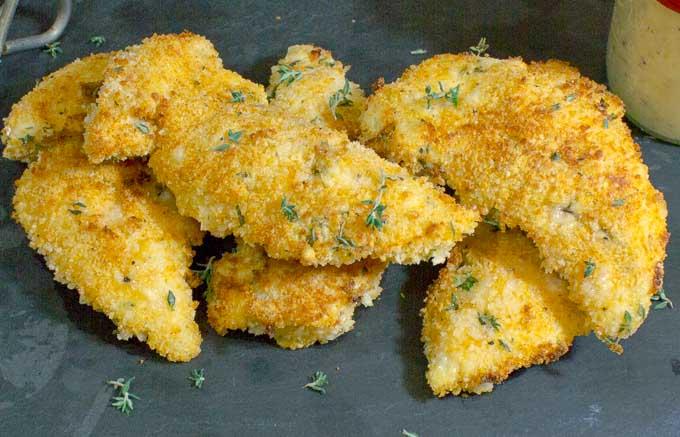 5 Healthy Buttermilk Baked Chicken Strips on black slate with honey mustard