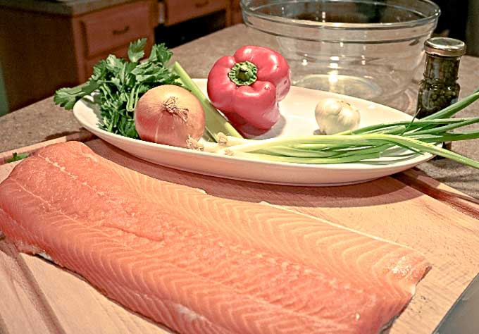salmon, onion, pepper, parsley ingrediants on a cutting board ready to be made into salmon cakes