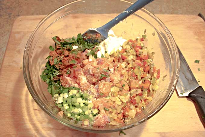 raw ingrediants for Baked Fresh Salmon Cakes in a glass bowl being stired together