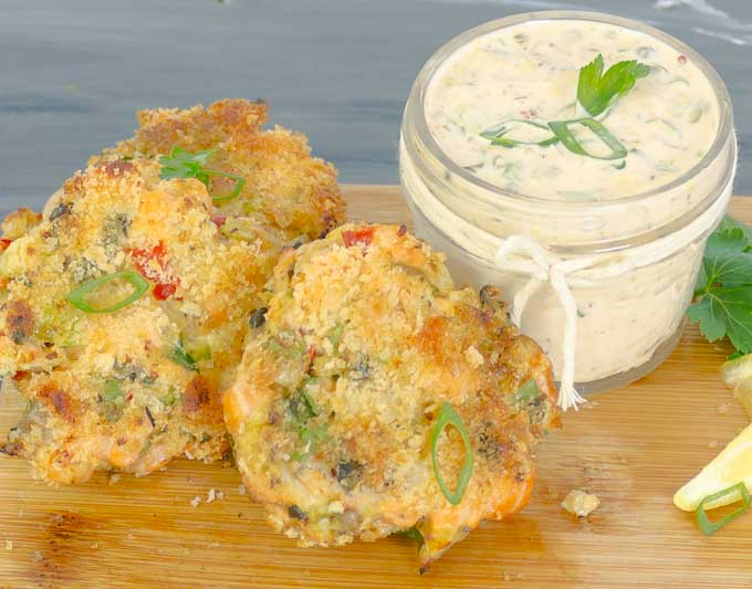 3 Baked Fresh Salmon Cakes (Salmon Patties) on wood board with spicy remoulade and a lemon slice
