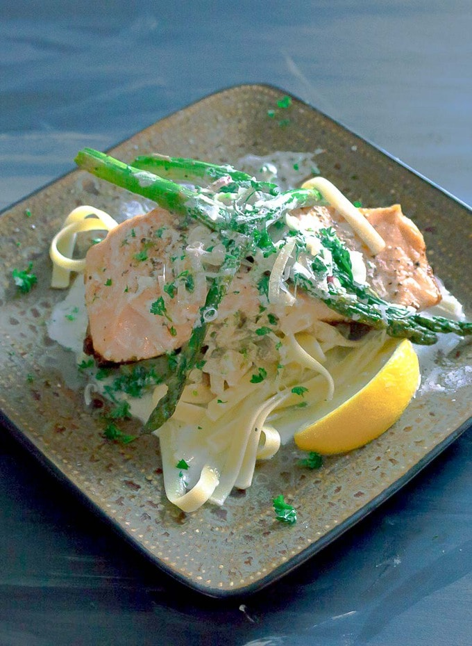 Salmon with Garlic Cream Sauce on square plate with asparagus and pasta