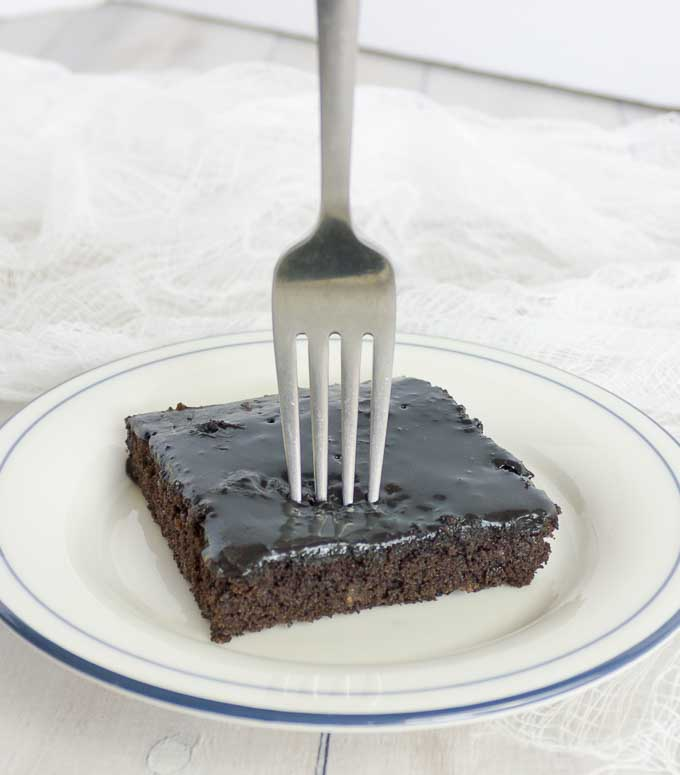 slice of Old Fashioned Buttermilk Texas Sheet Cake on white plate with fork