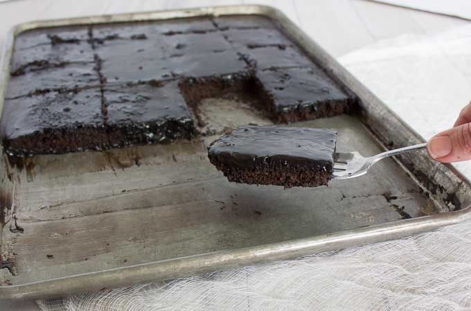 pan of Old Fashioned Buttermilk Texas Sheet Cake with a slice on a cookie sheet