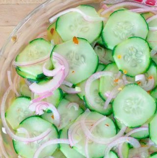 Pickled Cucumber and Red Onion Salad in clear bowl on a red cloth