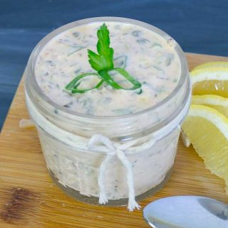 Spicy Remoulade Sauce in glass jar on wood cutting board with parsly, green onion, and lemon