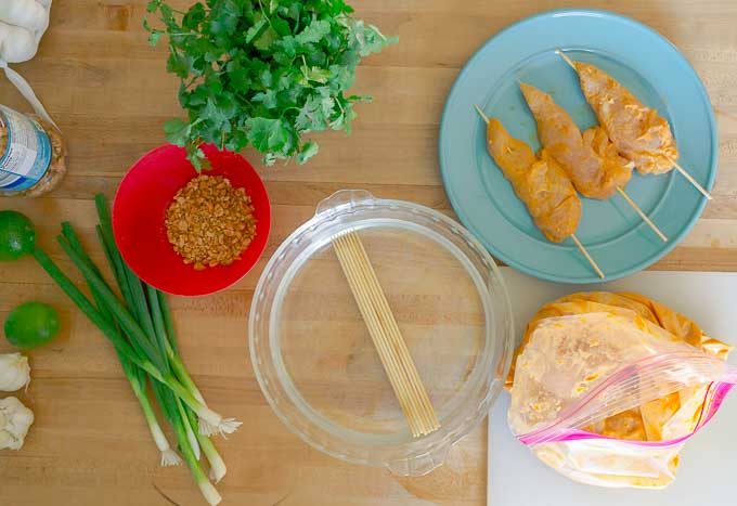 Thai Chicken Satay Skewers being marinated and put on a skewer