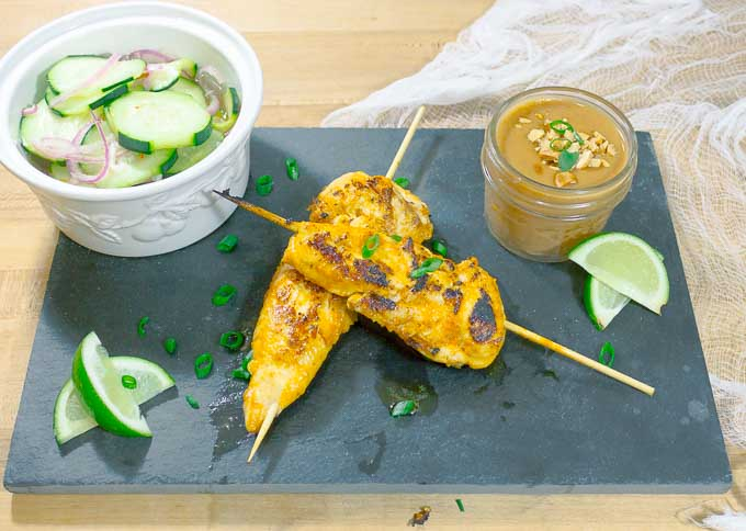 Thai Chicken Satay Skewers on blackslate with cucumbers and peanut sauce