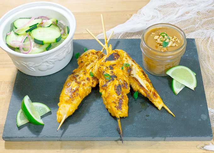 Thai Chicken Satay Skewers on blackslate with cucumbers and peanut sauce