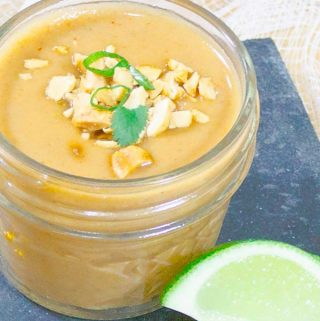 Thai Peanut Sauce Recipe in glad jar with peanut and green onion garnish