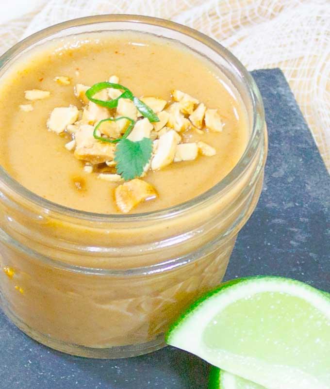 Thai Peanut Sauce Recipe in glad jar with peanut and green onion garnish