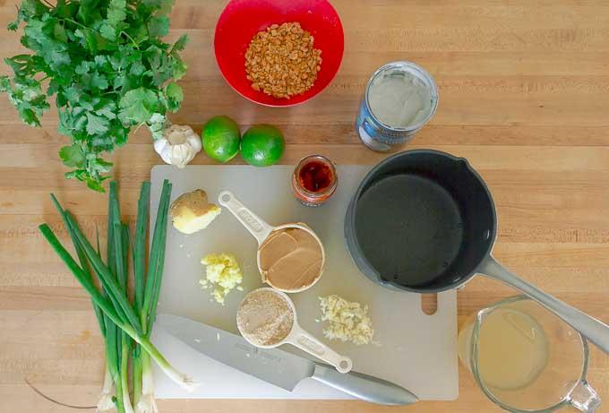 Thai Peanut Sauce Recipe ingrediantsbeing prepped an dmeasured on white cutting board
