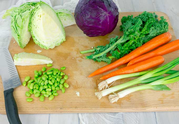 raw veggies on cutting board for salad