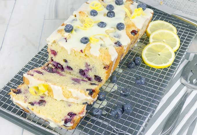 sliced Blueberry Lemon Sour Cream Pound Cake on wire rack with fresh blueberries