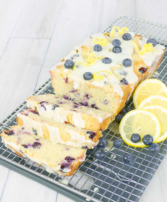 partially sliced Blueberry Lemon Sour Cream Pound Cake on wire rack with lemon slices