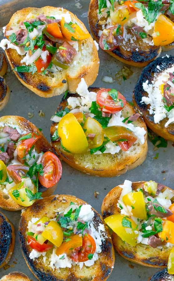 several slices of Grilled Goat Cheese Bruschetta topped with herb salad on a metal sheet