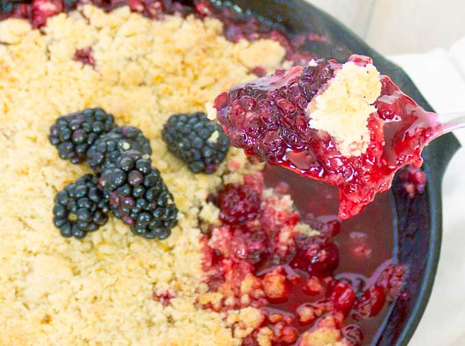 a spoonfull of Cast Iron Skillet Blackberry Crumble with the crumble in the background