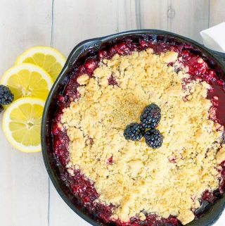 Cast Iron Skillet Blackberry Crumble on white wood with lemon slices