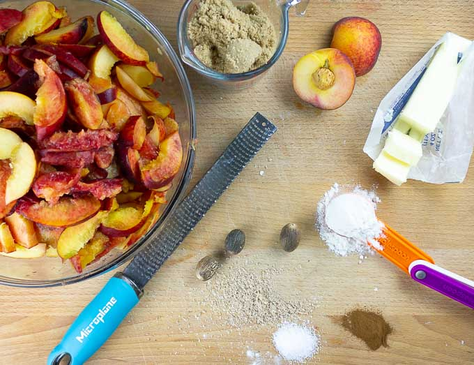 ingrediants for Fresh Peach Pie With Crumb Topping on a wooden surface