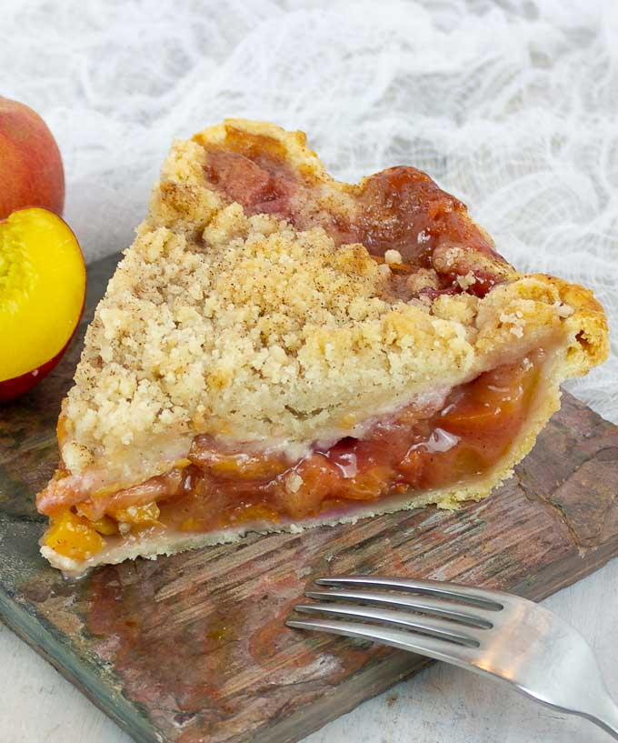 one slice of Fresh Peach Pie With Crumb Topping and the tines of a fork