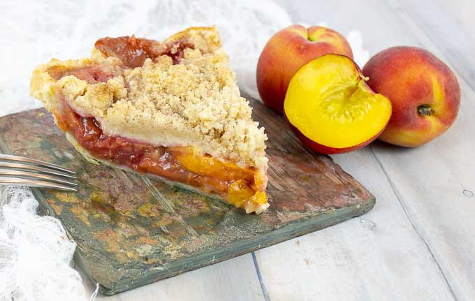 slice of Fresh Peach Pie With Crumb Topping on slate with whole peaches
