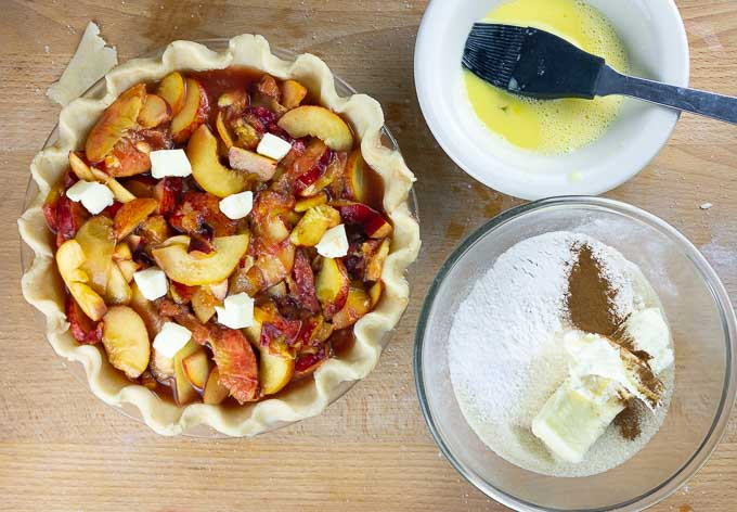 uncooked Fresh Peach Pie With Crumb Topping with bowl of egg wash