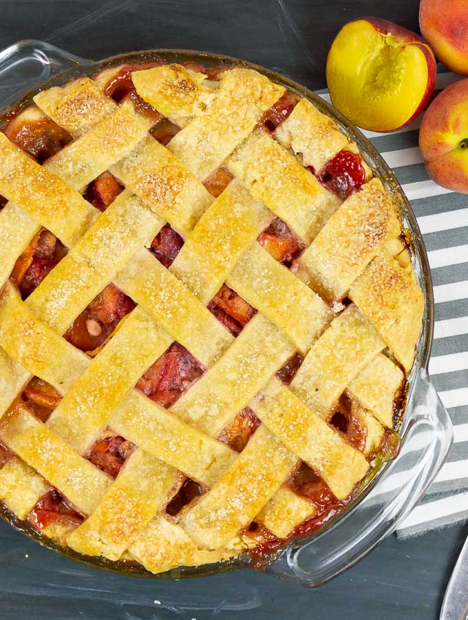 Fresh Peach Pie With Homemade Crust next to whole peaches