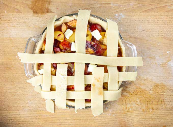lattice strips of dough being put on a peach pie
