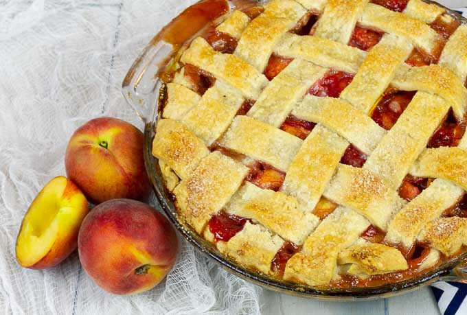 bottom left side of a Fresh Peach Pie With Homemade Crust with fresh peaches along side