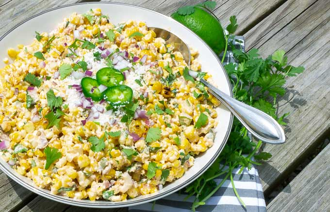 right side of a white bowl and spoon of grilled street corn salad