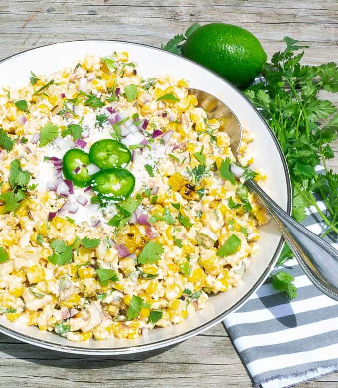 right side of a white bowl of Grilled Street Corn Salad with lime and cilantro