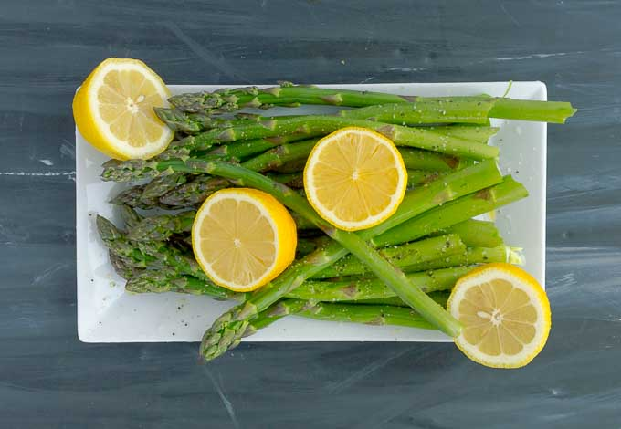 raw asparagus and fresh lemons cut in half