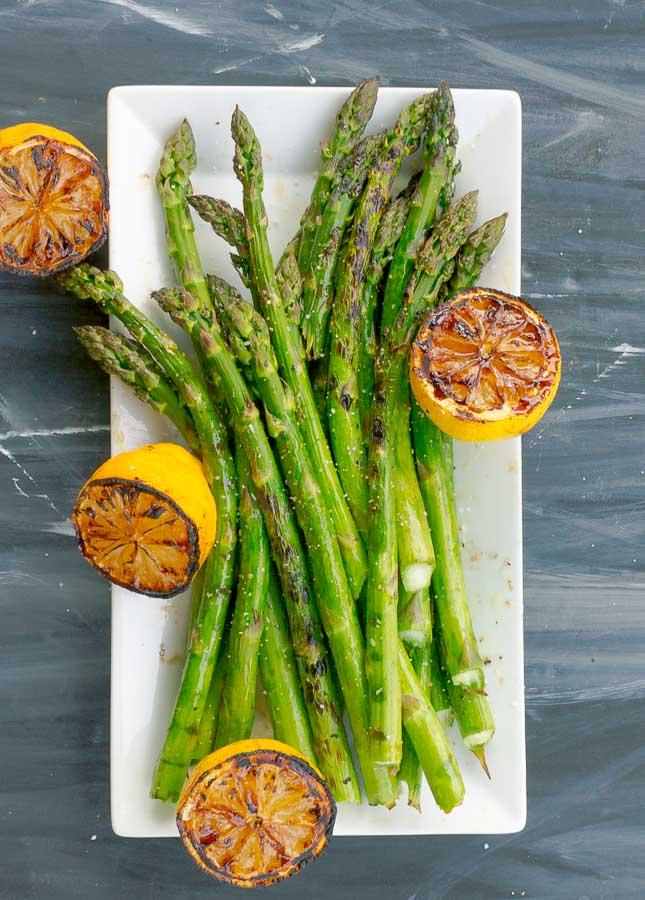 white platter of grilled asparagus and 4 lemon halves