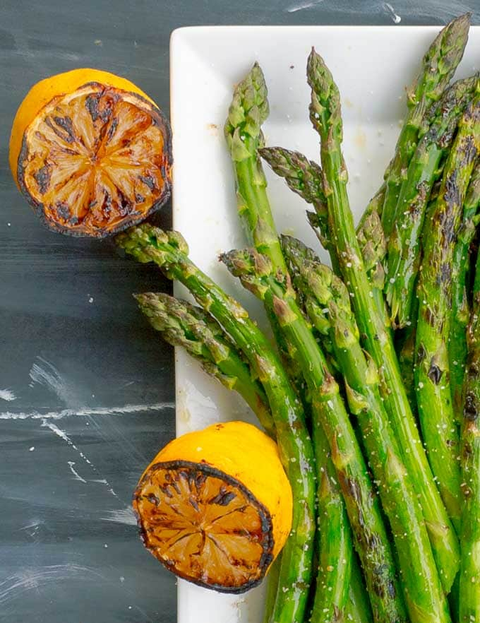 Grilled Asparagus with Grilled Lemon on white platter with 2 grilled lemons