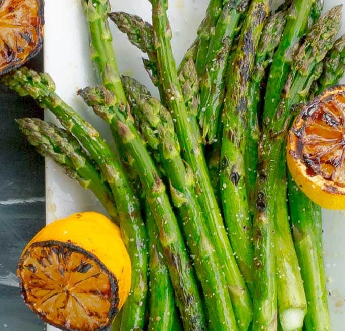Grilled Asparagus with Grilled Lemon on white platter