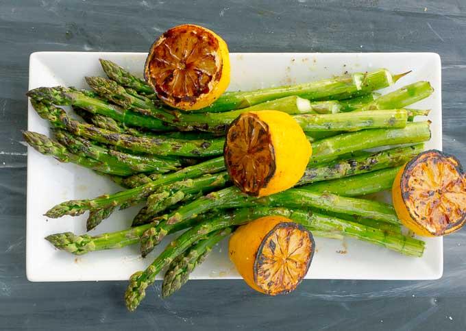 white platter of grilled asparagus and lemons