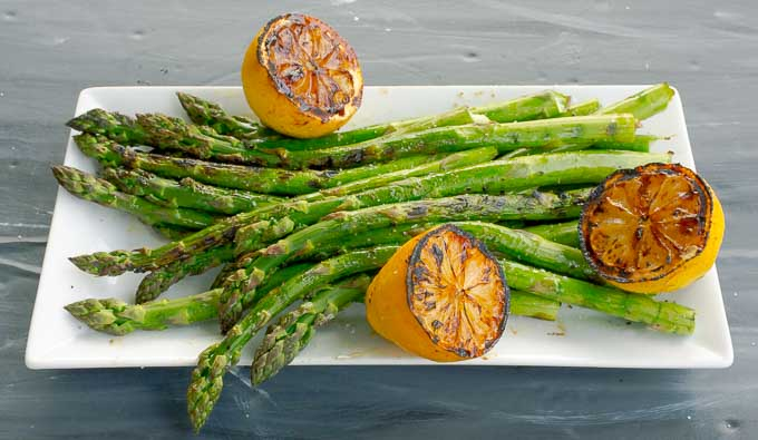 white platter of Grilled Asparagus with Grilled Lemons