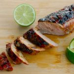 Smokey Brown Sugar Crusted Pork Tenderloin sliced on bamboo cutting board with lime wedges
