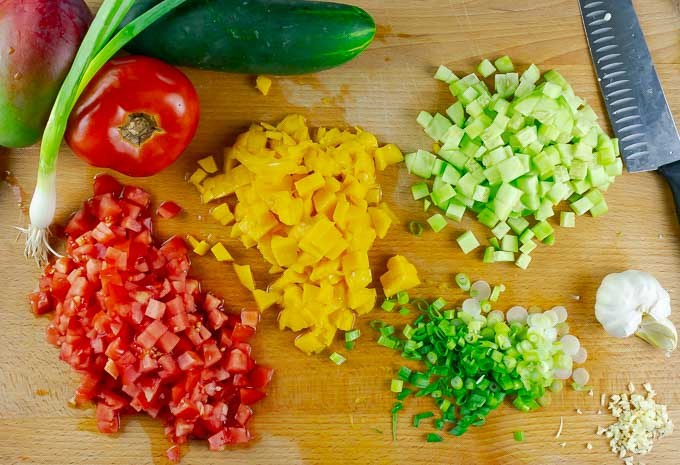 diced tomato, cucumber, mango, garlic, and sliced green onions on wooden cutting board