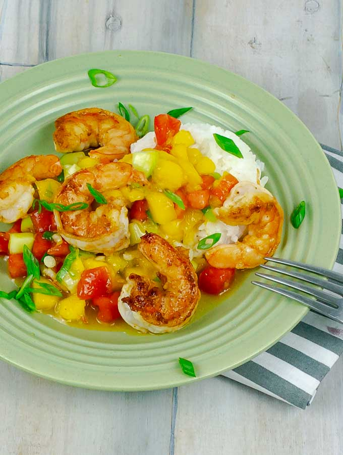 green plate of Garlic Shrimp with Mango Cucumber Salsa and Coconut Rice