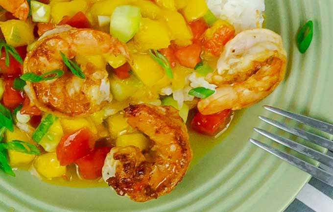 bottom right corner of green plate of Garlic Shrimp with Mango Cucumber Salsa and Coconut Rice