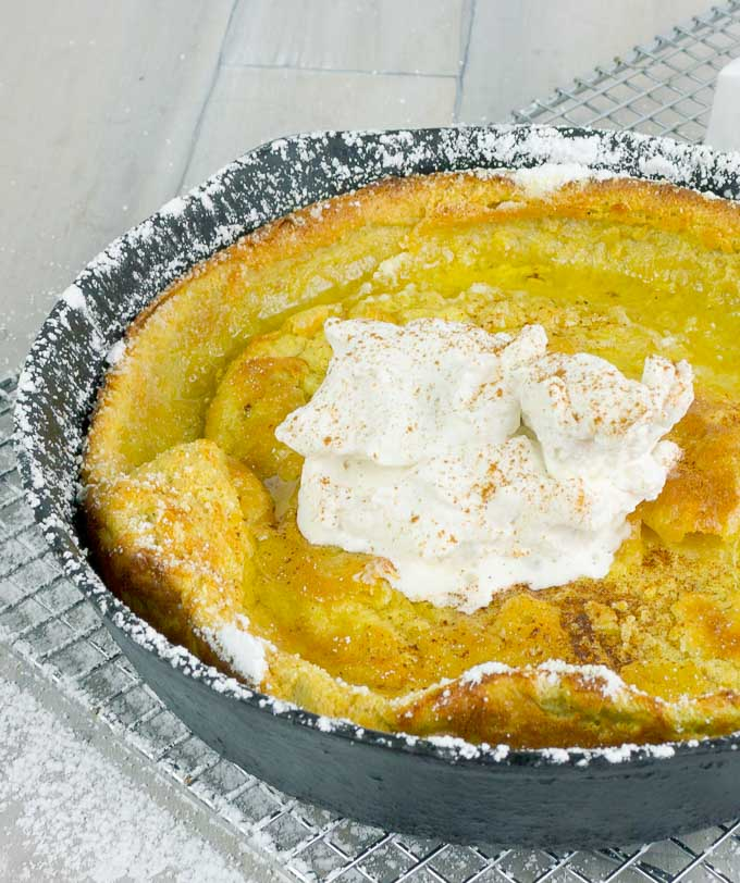 Pumpkin Pie Dutch Baby  in a cat iron skillet with whipped cream