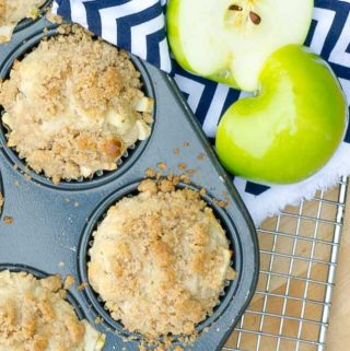 two apple streusel muffins and a sliced apple