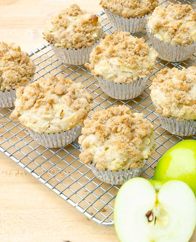Apple Streusel Muffins on cooling rack with a green apple