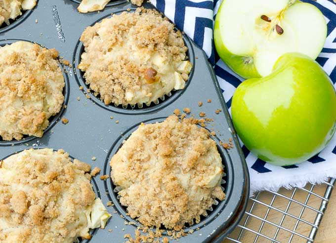 four apple streusel muffins in tin with a cut apple