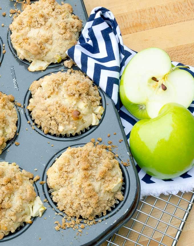 Apple Streusel Muffins in tin with blue napkin and apple