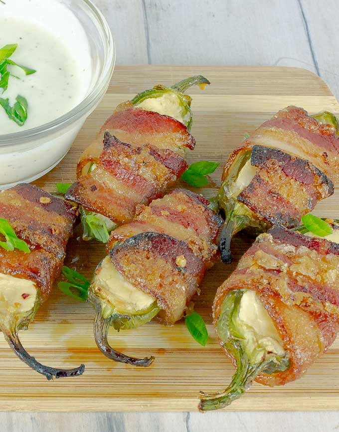 five Bourbon Candied Bacon Wrapped Jalapeno Poppers on wood with ranch